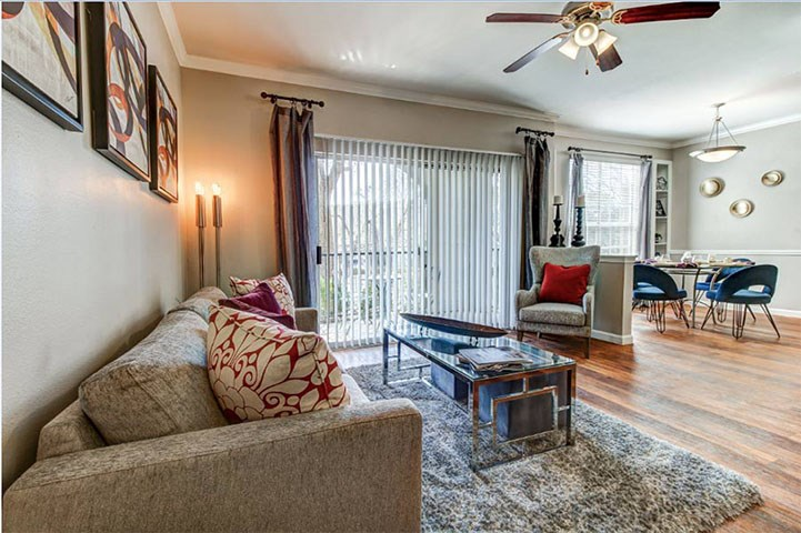 Living room with open dinning and kitchen areas, ceiling fan, balcony access and wood-style floors