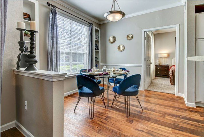 Dinning room with large window, wood-style flooring, and updated lighting leading to bedroom