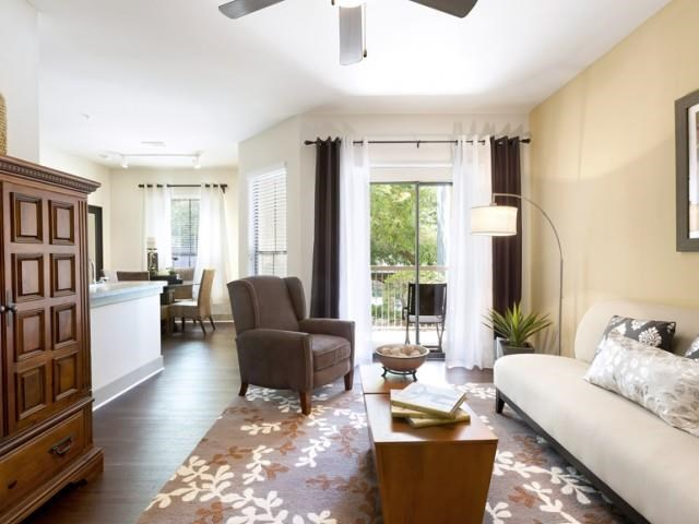 Living room with ceiling fan, wood-style floors and balcony access