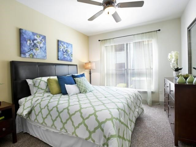 Bedroom with large windows, plush carpeting and ceiling fan