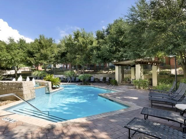 Pool surrounded by shade trees and lounge seating