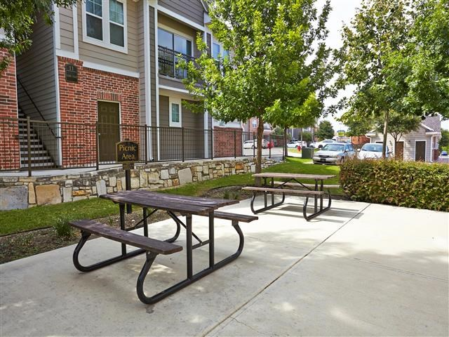 Outdoor courtyard with picnic table seating surrounded by trees