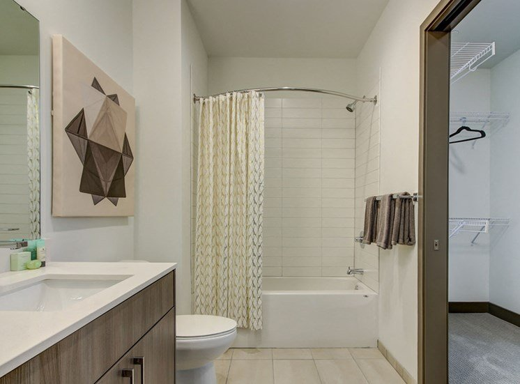 Kansas City MO Apartments-The Grand Apartments Bathroom With White Countertop And Square Tile And Neighboring Closet