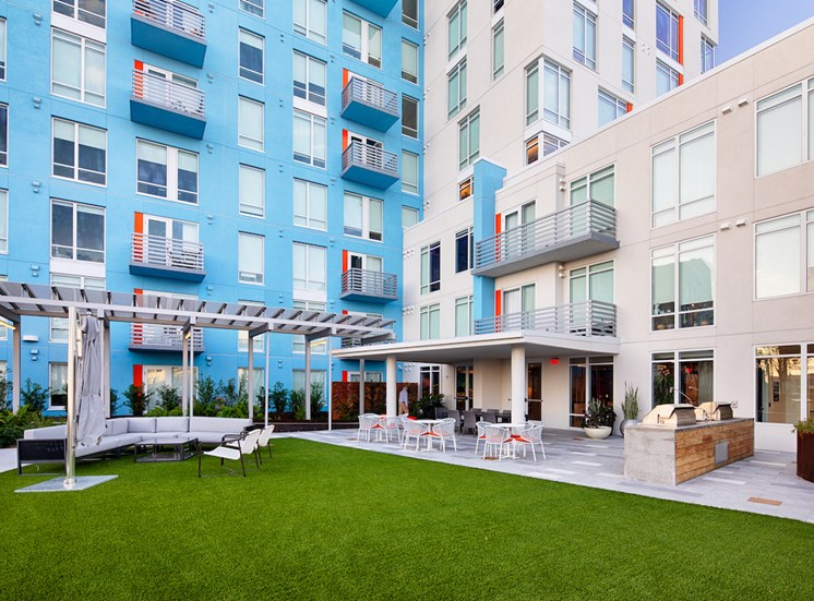 Apartments overlooking outdoor kitchen and lounge on amenity deck