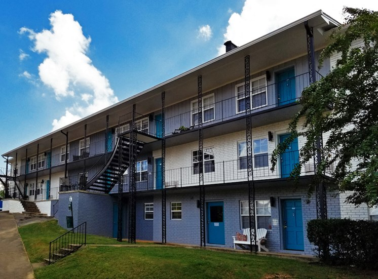 Murals apartments with alternating paint colors and blue sky with clouds