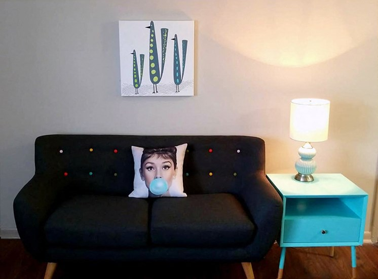 living room with couch, side table, lamp, and decor