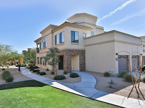 Exterior of apartment building with lawn and desert landscaping