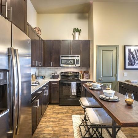 Kitchen with espresso colored cabinets, brushed nickel appliances, and a table with chairs
