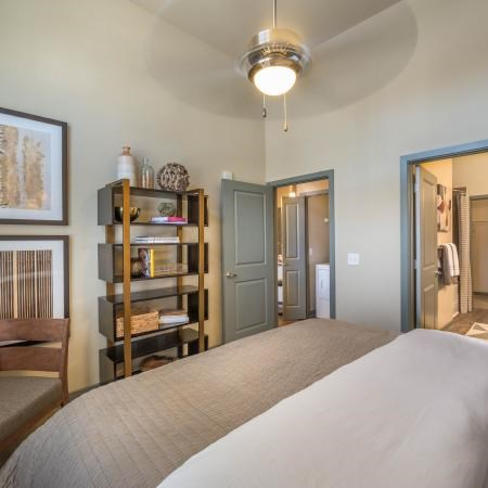 Bedroom with full size bed, ceiling fan, framed decorations on wall, and an en-suit bathroom