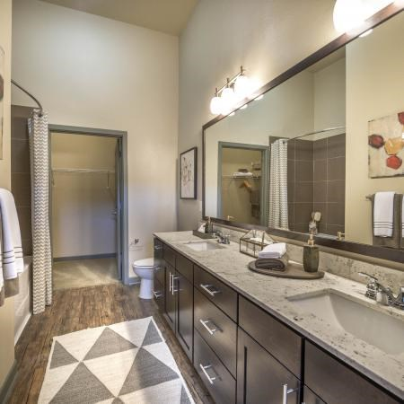 Bathroom with hardwood style flooring, vanity light bulbs, and oversized counter spaces