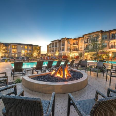 Fire pit positioned next to pool, evening time scenic view, building exterior in the background