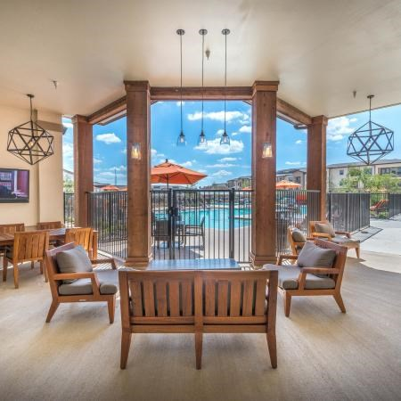 Clubhouse interior with stunning pool side view and a lounge area with chairs