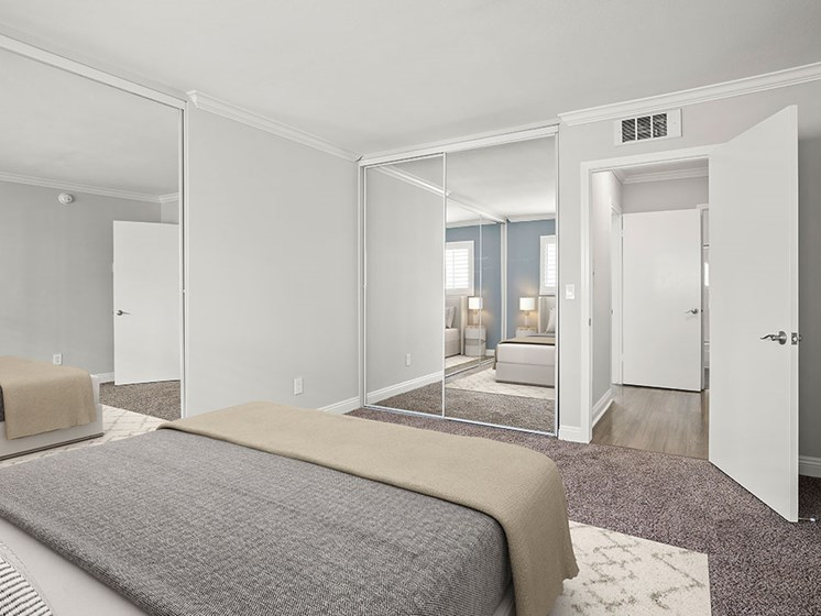 Carpeted bedroom with copious closet space.