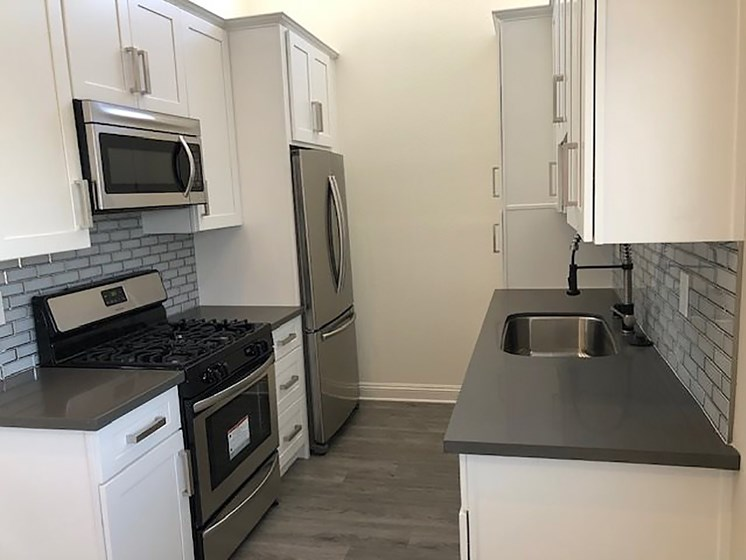 Tiled kitchen with stainless steel fridge, oven, and microwave.