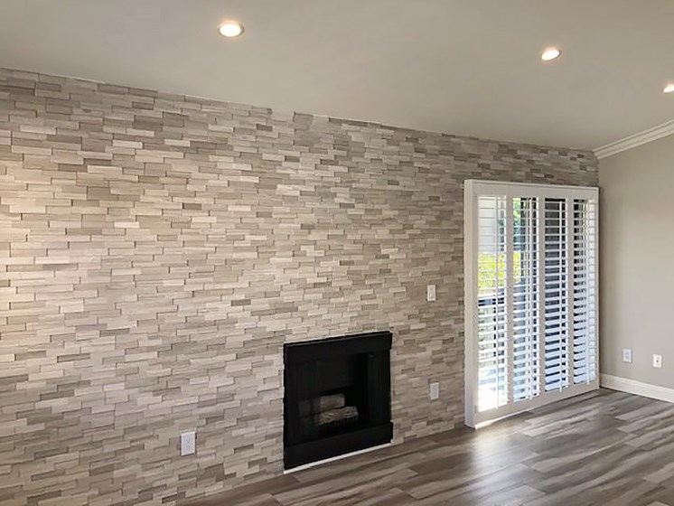 Stone accent wall and fireplace with large adjacent windows.