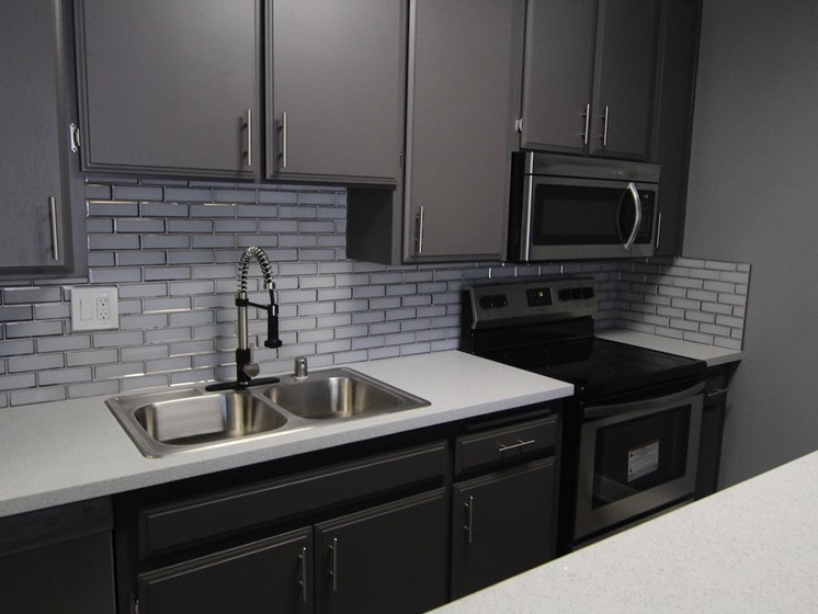 White tiled kitchen with stainless steel fridge, microwave, and oven.