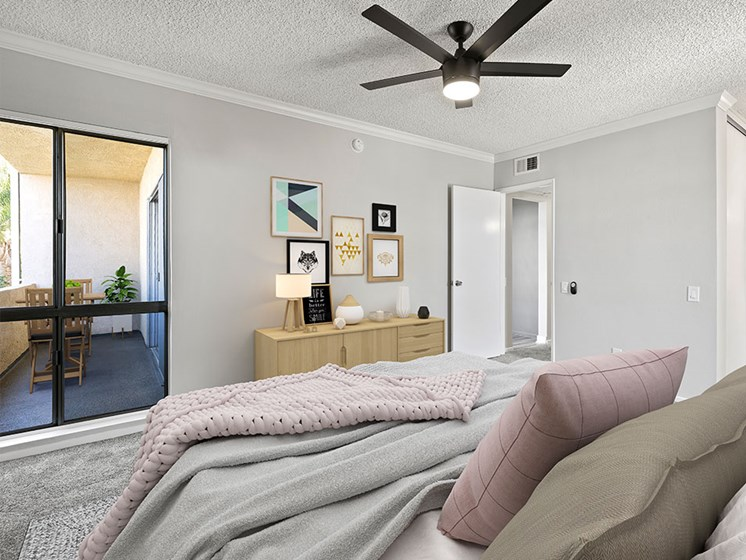 Carpeted bedroom with ceiling fan and natural light from adjacent patio.