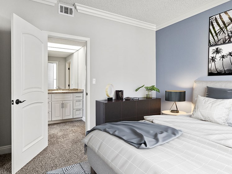Carpeted bedroom with private bathroom.