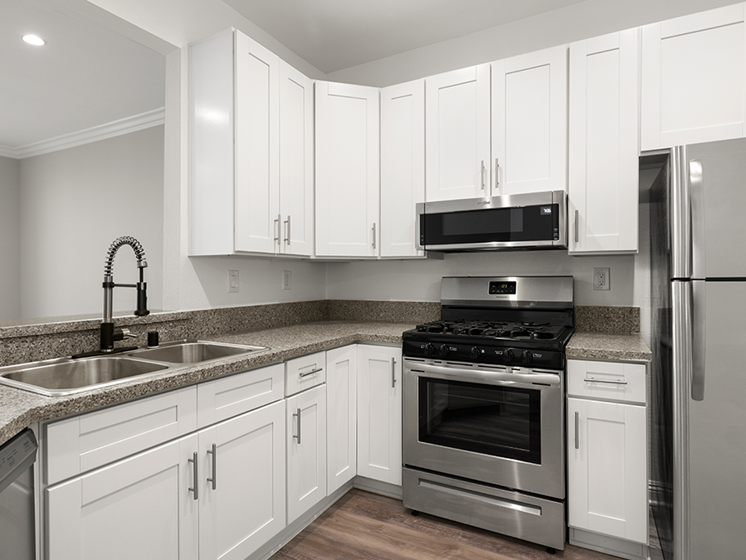 Kitchen with stainless steel fridge, oven, and microwave.