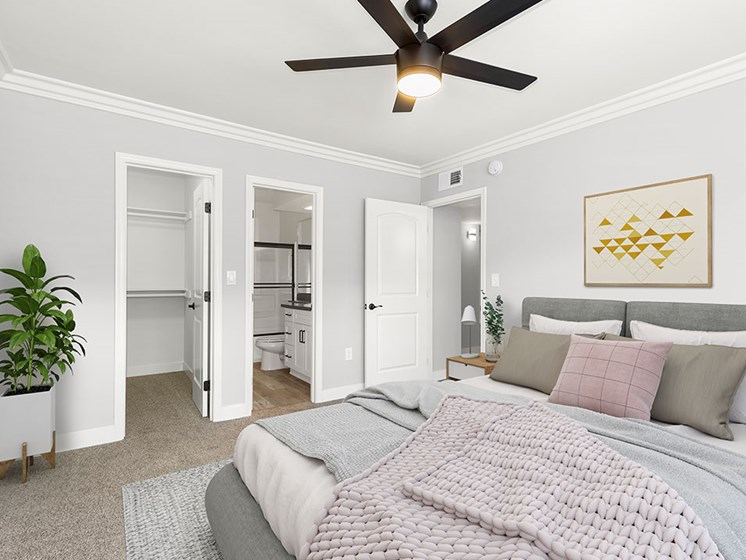 Carpeted bedroom with ceiling fan and private bathroom.