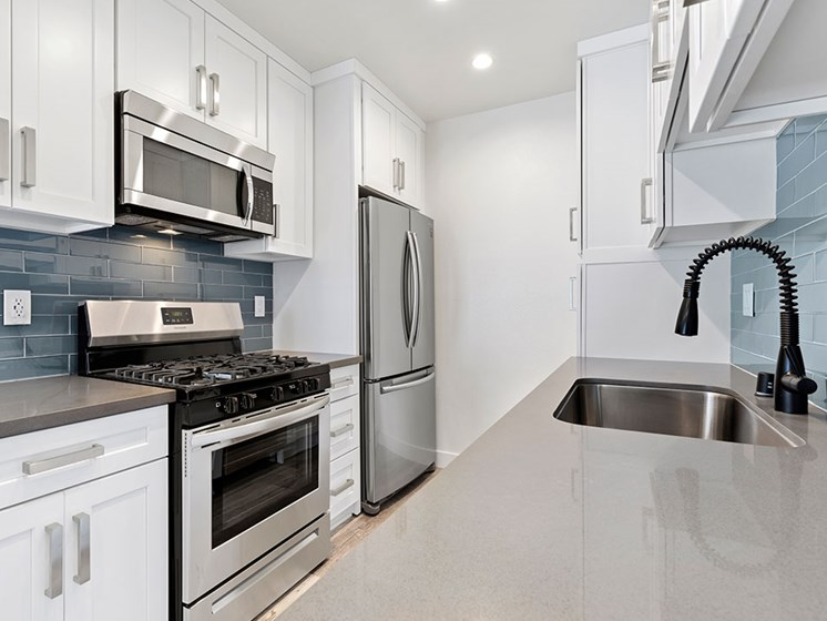 Blue tiled kitchen with quartz stone counters and stainless steel microwave, oven, fridge, and fixtures.