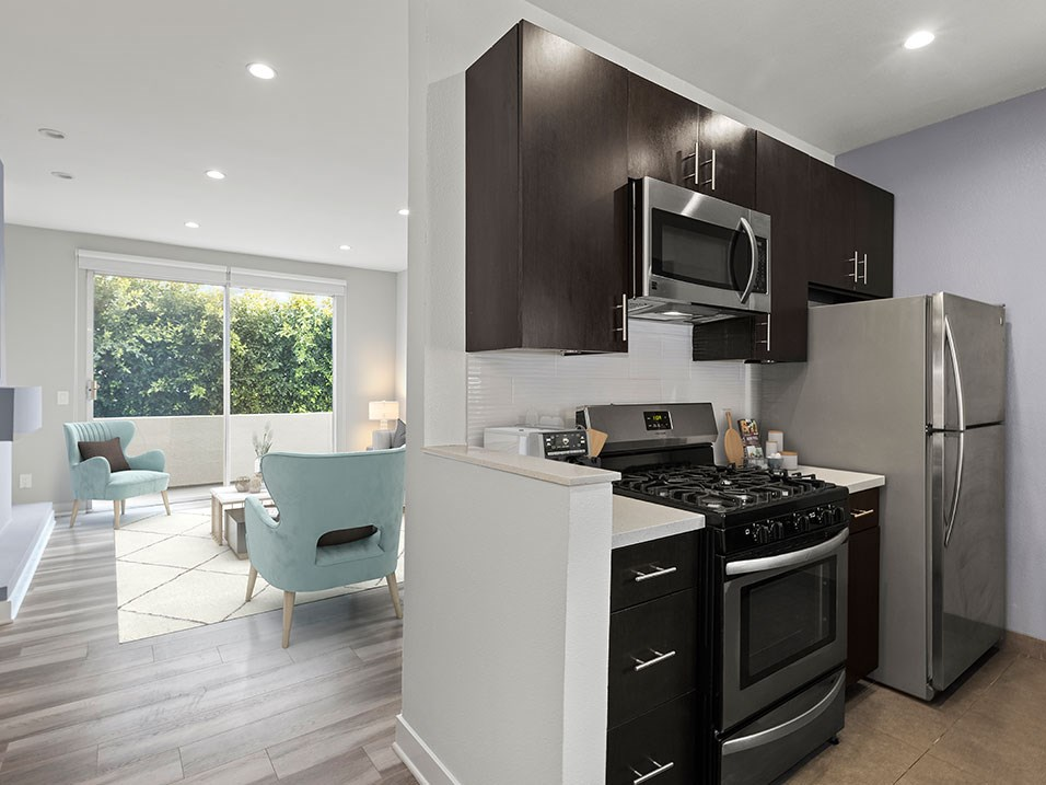 White tile kitchen with granite countertop and stainless steel fridge, oven, and fixtures.