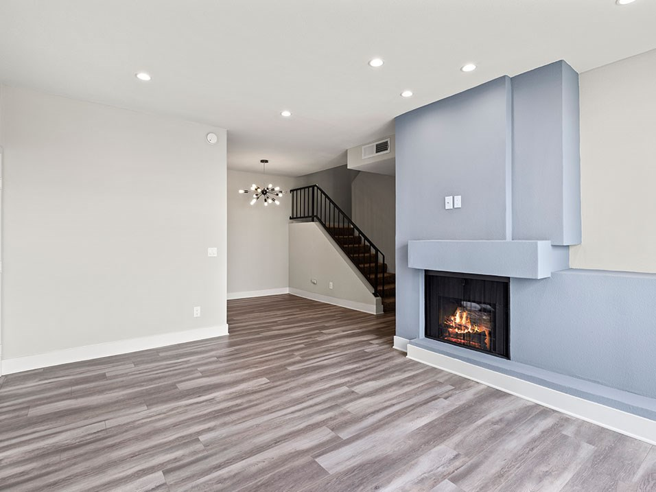 Living room with hardwood floor, fireplace, and access to upstairs loft.