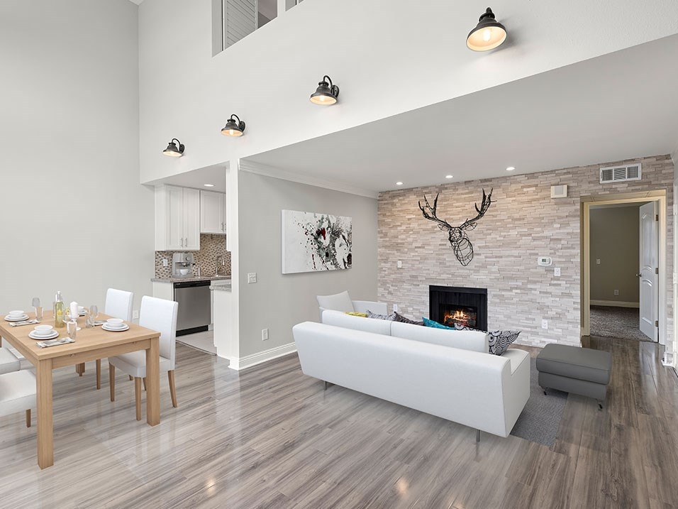 Living room with decorative stone wall and view of loft overhead.