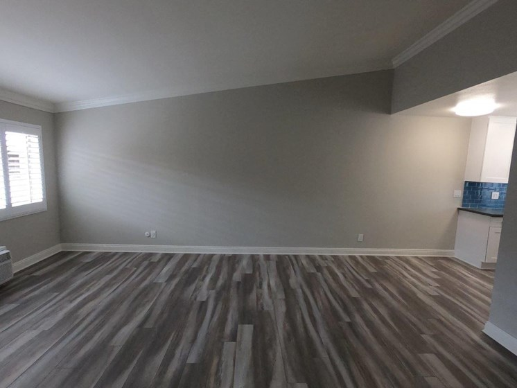 View of hardwood laminate flooring in living room and dining room.