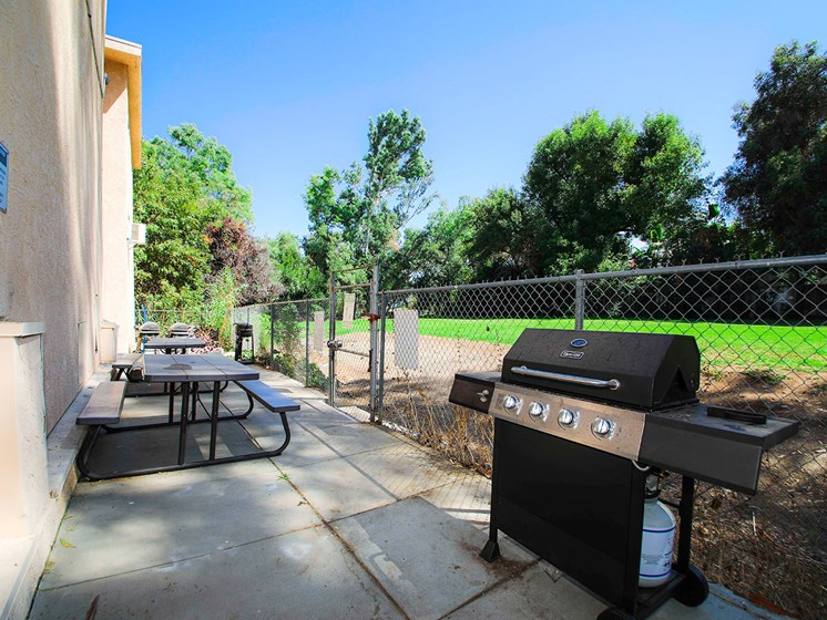 Outdoor barbeque space adjacent and connected to neighboring park space.