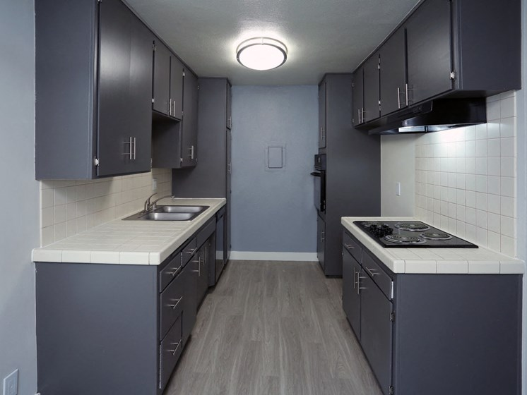 Kitchen with white tile backsplash and stainless steel fridge, oven, and microwave.