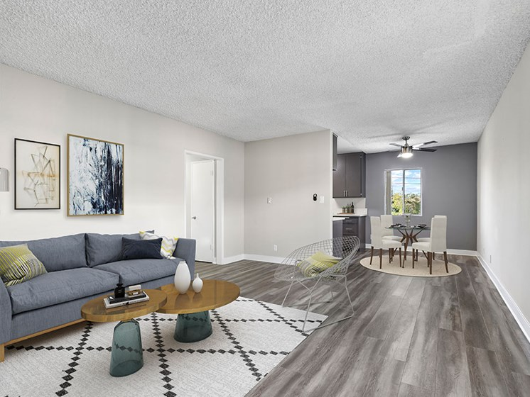 Spacious hardwood floor living room with view of dining area.