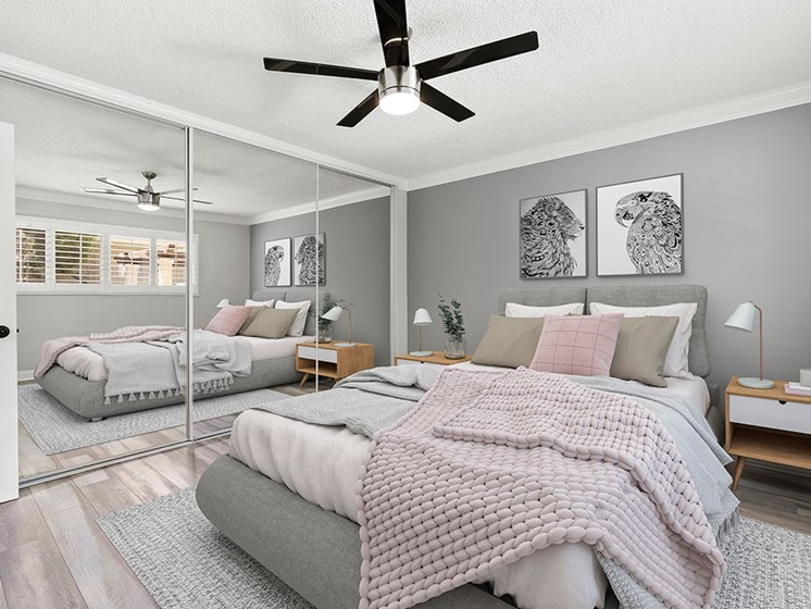 Carpeted bedroom with ceiling fan and large mirrored closet.