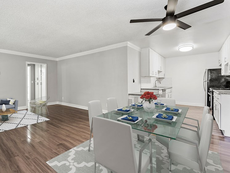 Large hardwood floored dining room with view of kitchen.