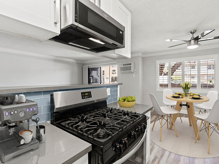Blue tiled kitchen with stainless steel oven and microwave and view of hardwood floor dining room.