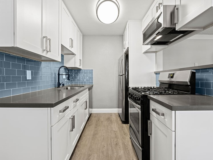Blue tiled kitchen with stainless steel oven, microwave, and fridge.