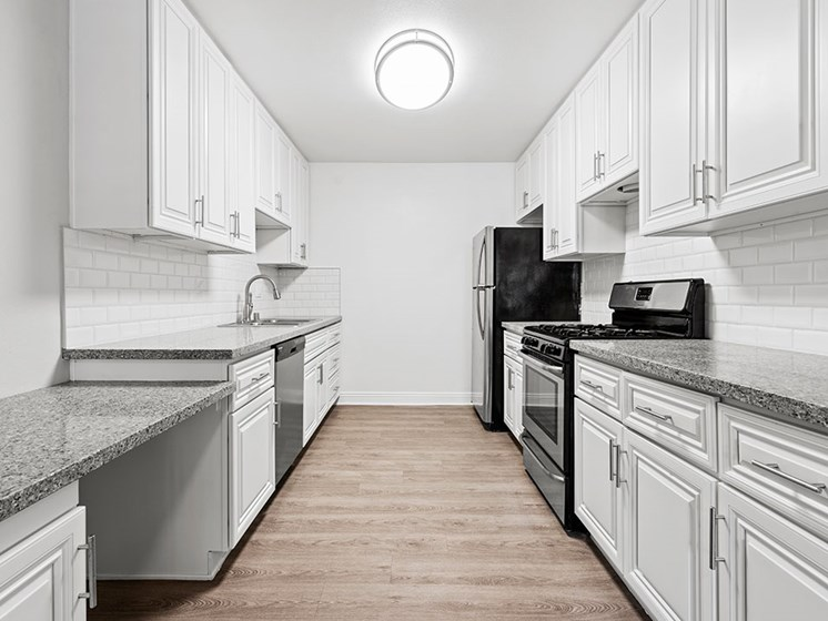 Large white tiled kitchen with stainless steel oven, microwave, and fridge.