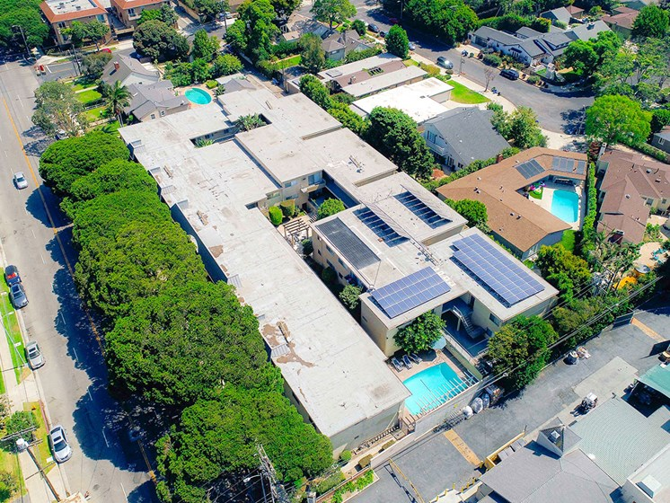 Aerial drone view of National Apartments depicting roof-mounted solar panels and adjacency to Whole Foods Market.