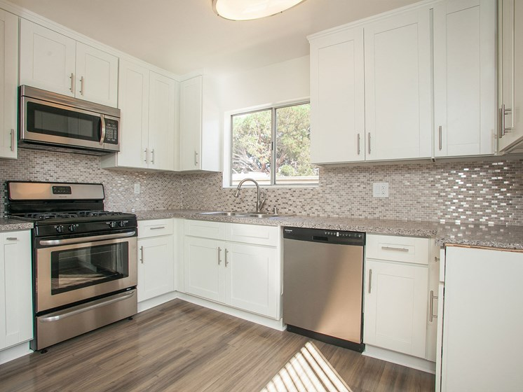 Large kitchen with new cabinets, stainless steel appliances, quartz stone counters, and modern backsplash.