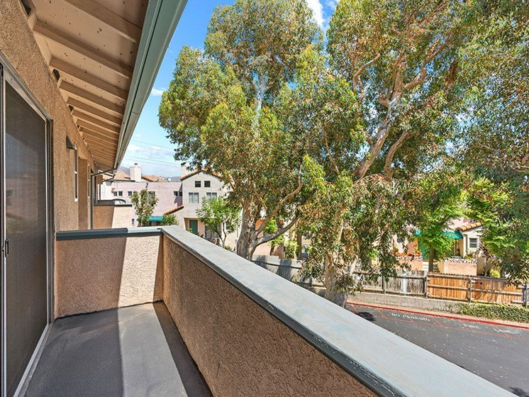 Private balcony with view of tree lined surrounding community.