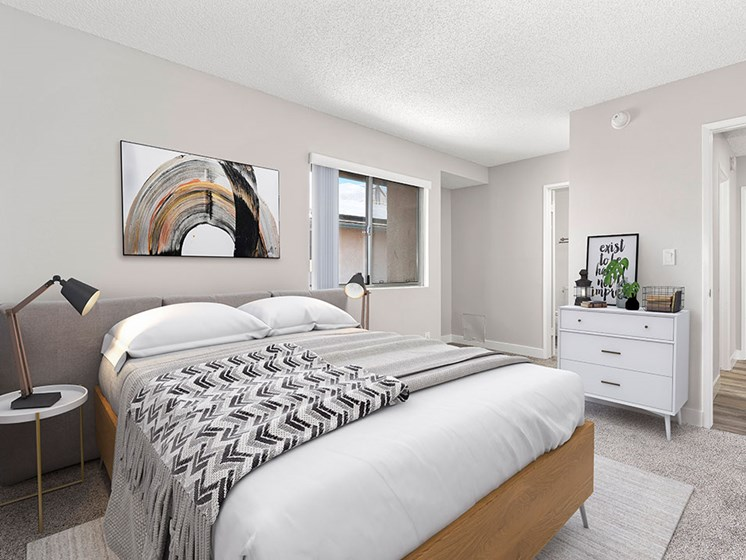 Carpeted bedroom with private bathroom and large exterior windows.
