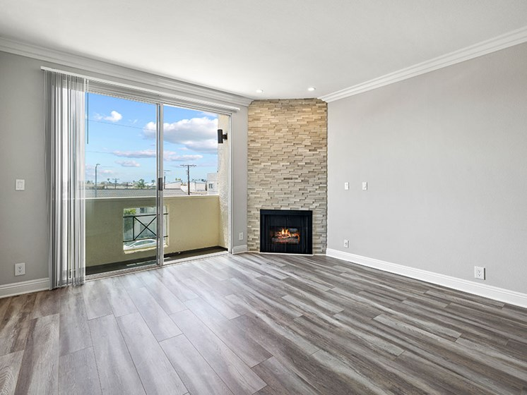 Hardwood floored living room with stone walled fireplace and balcony.