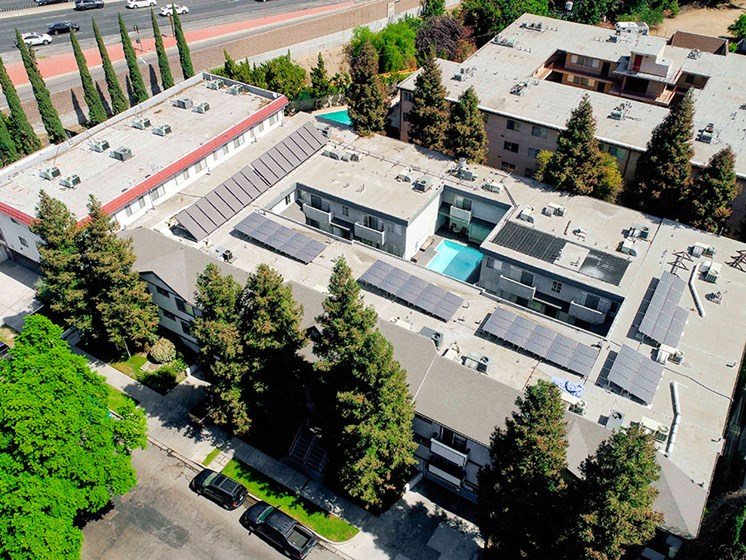 Aerial drone image of building with view of solar panels.