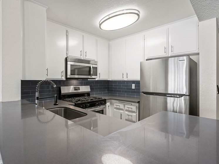 Kitchen with stainless steel oven, microwave, and fridge.