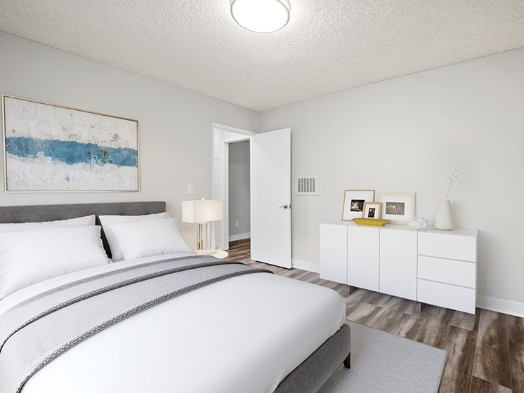 Hardwood floored bedroom with private closets and ceiling-mounted light fixtures..
