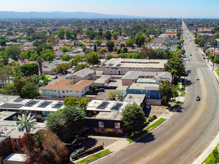 Aerial drone photo of 10620 NoHo showing solar panels and energy-efficient white roofing.