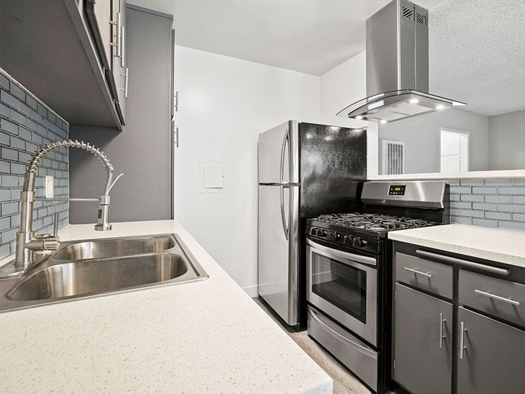 Blue tiled kitchen with stainless steel fridge, oven, and fixtures.