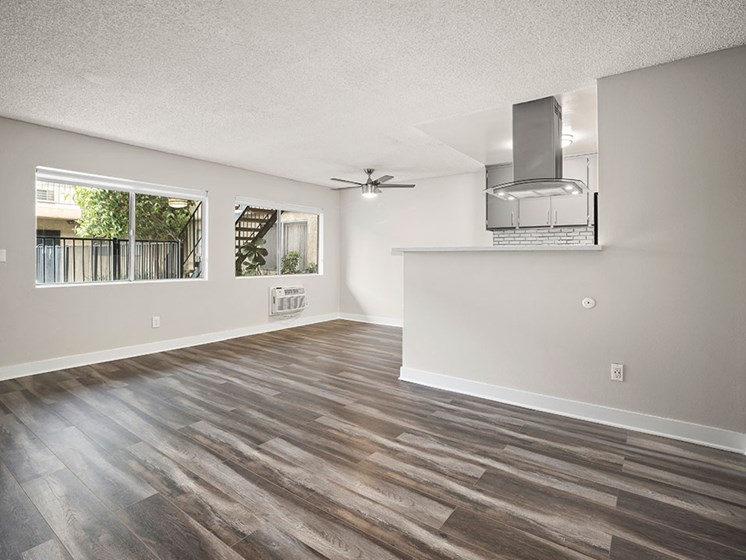 Large hardwood floored living room with ceiling fan over dining room.