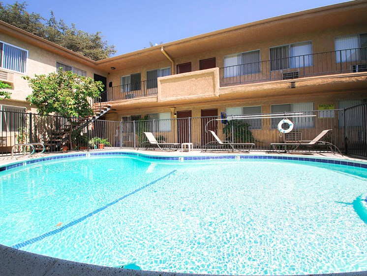 View of gated community pool with lounging space.