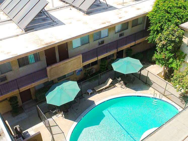 Aerial view of gated community pool with lounging space.